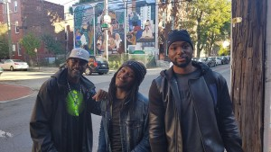 Three men smiling in front of a mural