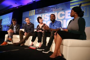 """Panelists sitting on the stage in front of a """"Justice in America"""" sign"""
