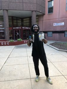 Jason Reynolds stands outside the DC jail holding copies of his books Long Way Down and When I Was the Greatest