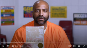 Free Minds member Rodney in an orange jumpsuit holds a copy of The Giver