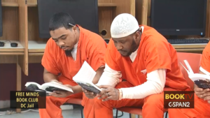 Two men in orange jumpsuits reading The Things They Carried