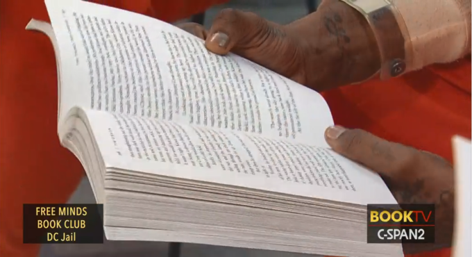 A close up of hands holding open a copy of the book The Things They Carried