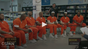 A group of men in orange jumpsuits sitting in a row with books