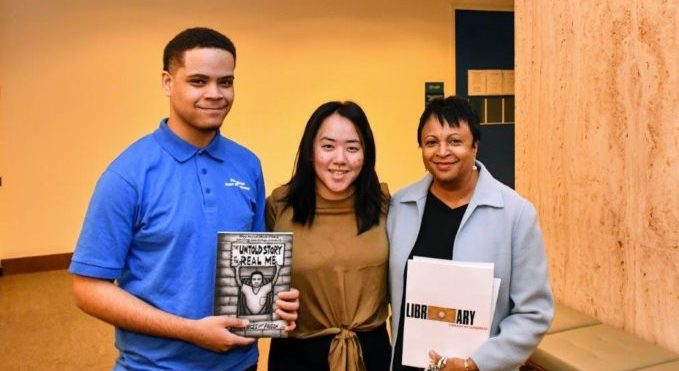 Three people stand in a row holding a book called The Untold Story of the Real Me