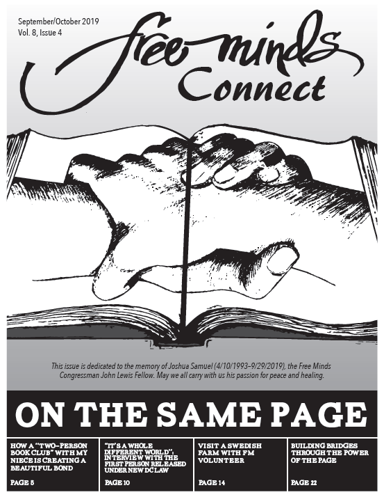 Free Minds Connect: On the Same Page. Image of an open book with two clasped hands printed on the pages.